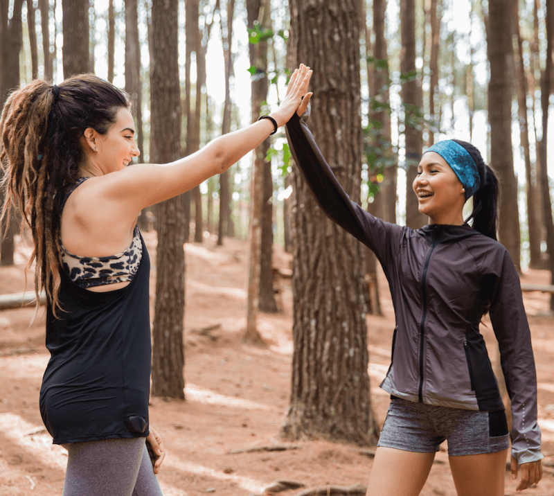Two women hiking and high fiving each other